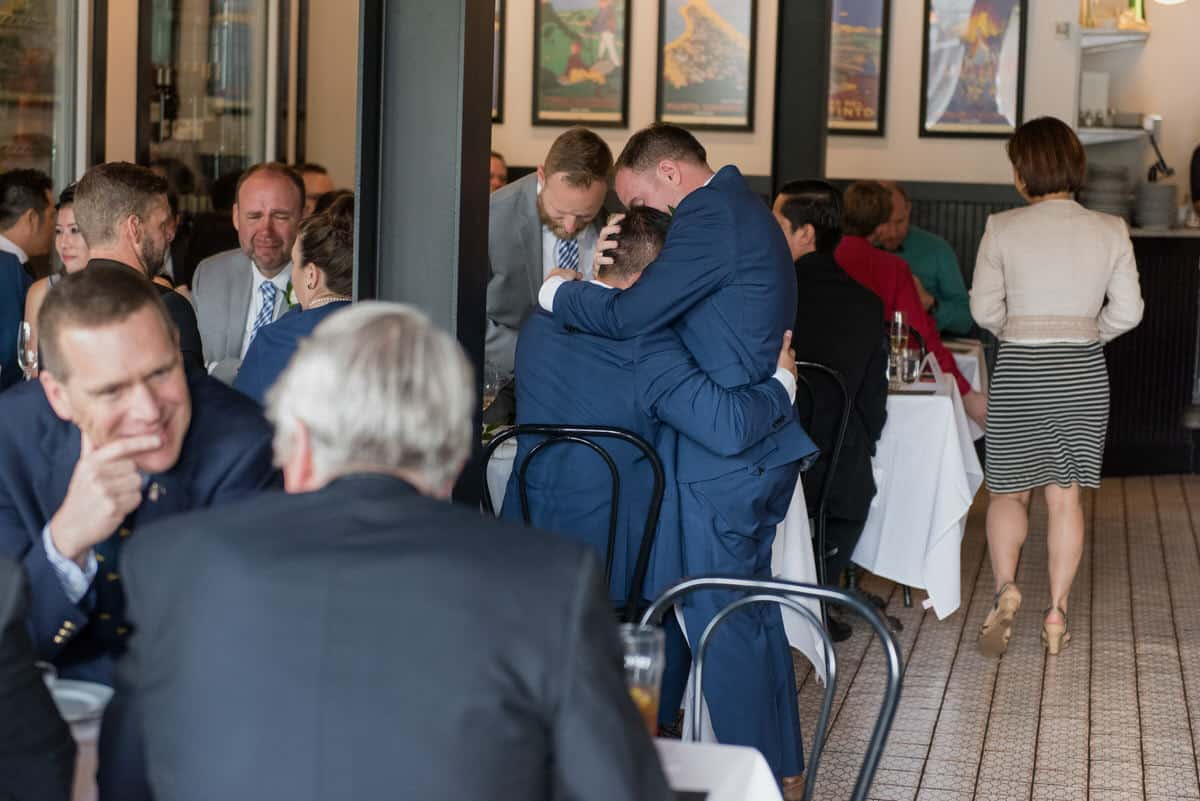Two grooms hugging and crying at wedding reception.
