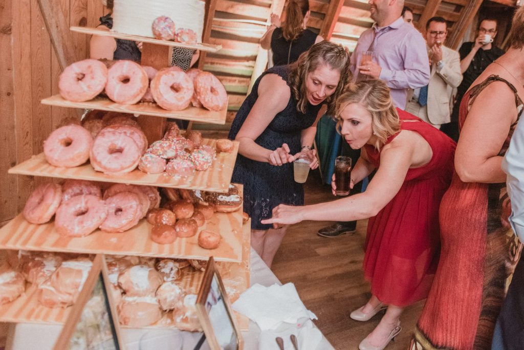 Guests looking at dessert from District Doughnuts on a custom made wooden display stand.