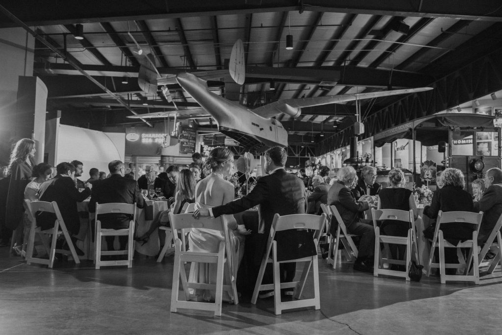 A black and white view of a wedding couple with a plane hanging from the ceiling at the Baltimore Museum of Industry.